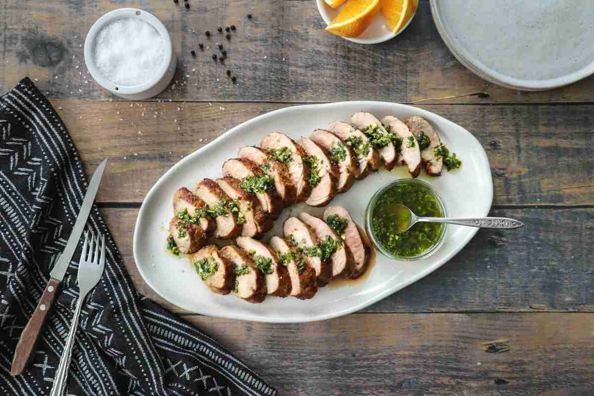 Dans une grande assiette à partager, des tranches de filet de porc mariné à l'orange et au cumin, nappées d'une sauce verte à la coriandre
