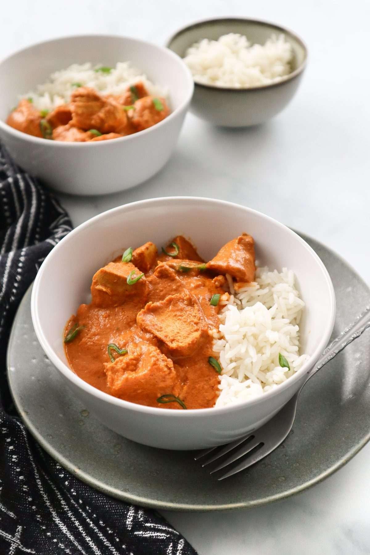 Deux bols de poulet au beurre crémeux, cuit à l'autocuiseur (Instant Pot) servi avec du riz blanc