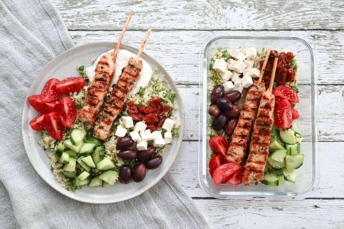 Assiette et plat de lunch de bol repas mezze avec brochettes souvlaki, tomates, concombres, olives, feta et couscous