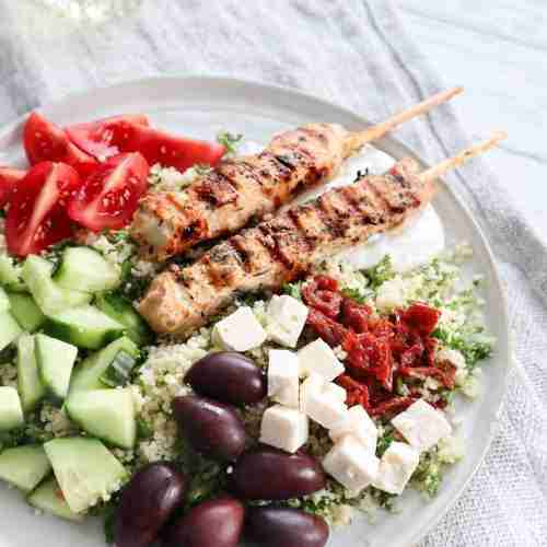 Assiette avec un fond de couscous garni de brochettes de poulet, de feta, de concombre, tomates, olives noires et tomates séchées